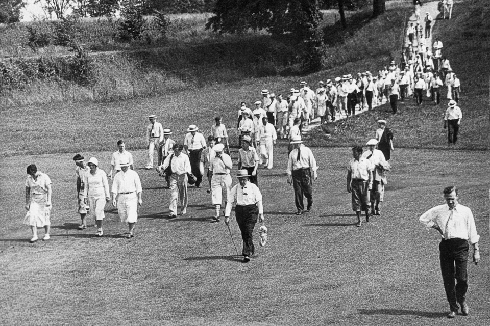 Spectators walking along the fairway