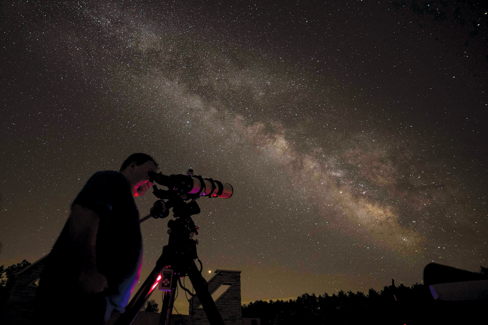 Man at JGAP looking at through a telescope at the night sky (photo by Brad Hoehne)