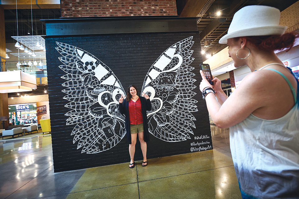 Woman posing with Kelsey Montague mural (photo by Todd Joyce)