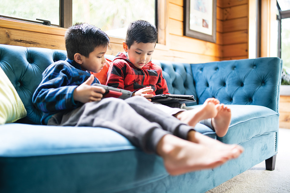 Children looking at iPads on a couch (photo by iStock)