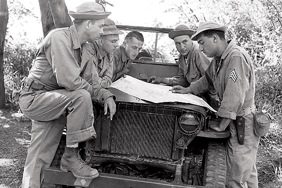 U.S. soldiers in the Pacific checking map on Willys MB slat-grille jeep