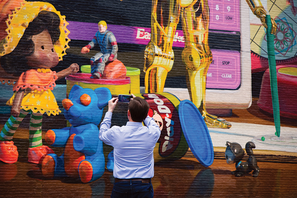 Editor Jim Vickers in front of Cincinnati's toy heritage mural (photo by Stephanie Park)